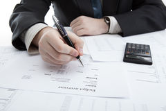 Businessman holding a pen and counts the budget Stock Photos