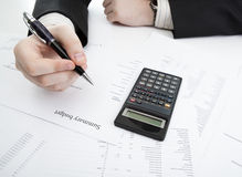 Businessman holding a pen and counts the budget Royalty Free Stock Photo