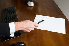 Businessman holding a pen over a blank paper sheet Royalty Free Stock Photos