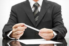 Businessman holding pen over proposed contract and thinking Royalty Free Stock Photo
