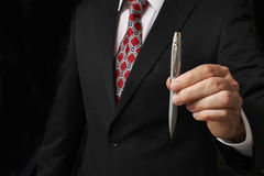 Businessman holding pen. Businessman in suit holding out pen towards camera stock photography