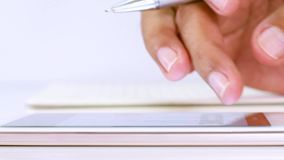 A businessman holding a pen and touching screen of a mobile phone for searching business data. A business man holding a pen and touching screen of a mobile stock footage