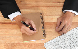 Businessman holding pen for writing on a notebook. Stock Image