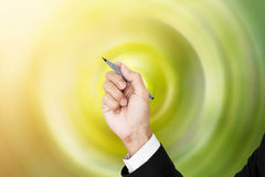 Businessman holding pen in writing position, with green spiral radial background Royalty Free Stock Photos