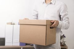 Businessman holding personal items box ready moving leaving Stock Photo