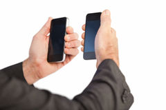 Businessman holding a phone in each hand Stock Images