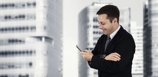 Businessman Holding Phone While Smiling and Feeling Happy With Business City and Corporate Buildings In Background royalty free stock photography