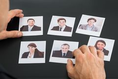 Businessman holding photograph of a candidate. Close-up Of A Businessman Holding Photograph Of A Female Candidate royalty free stock image