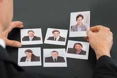 Businessman holding photograph of a candidate. Close-up Of A Businessman Holding Photograph Of A Female Candidate royalty free stock photography