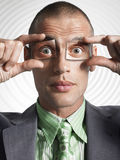 Businessman Holding Photos Of Eyes Over His Eyes Royalty Free Stock Image