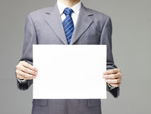 Businessman holding a piece of blank paper Stock Photos