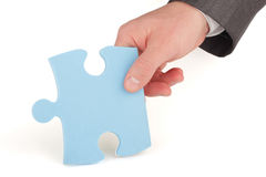 Businessman holding a piece of blue puzzle Royalty Free Stock Images