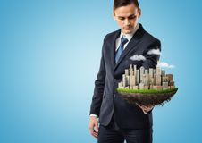Businessman holding piece of earth model wih city skyscrapers on blue background royalty free stock photos