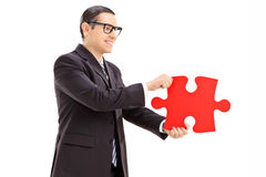Businessman holding a piece of puzzle Stock Image