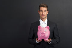 Businessman holding piggy bank Royalty Free Stock Photos