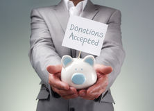 Businessman holding piggy bank for charity. Businessman holding piggy bank donation box for charity fundraising, investment or venture capitalist loan Royalty Free Stock Image