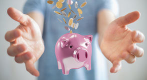 Businessman holding piggy bank with flying coins going inside 3D. Businessman on blurred background holding piggy bank with flying coins going inside 3D Stock Photo