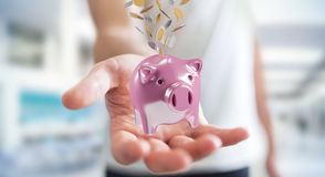 Businessman holding piggy bank with flying coins going inside 3D. Businessman on blurred background holding piggy bank with flying coins going inside 3D Stock Image