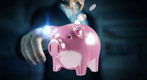 Businessman holding piggy bank with flying coins going inside 3D. Businessman on blurred background holding piggy bank with flying coins going inside 3D Stock Photos