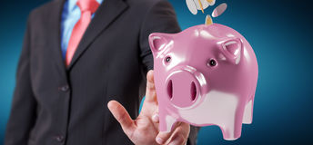 Businessman holding piggy bank with flying coins going inside 3D Stock Photos