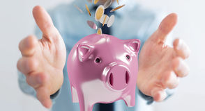Businessman holding piggy bank with flying coins going inside 3D. Businessman on blurred background holding piggy bank with flying coins going inside 3D Royalty Free Stock Image