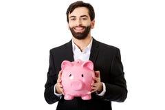 Businessman holding a piggy bank. Stock Photos