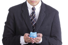 Businessman holding Piggy bank officer put money inside Stock Images