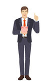 Businessman holding a piggy bank and pointing up Royalty Free Stock Photo