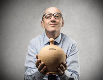 Businessman holding a piggy-bank stock image