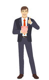 Businessman holding a piggy bank and showing thumb up Stock Photography