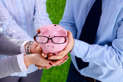 Businessman holding piggy box ,standing in office Royalty Free Stock Photos