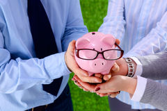 Businessman holding piggy box ,standing in office Royalty Free Stock Photo