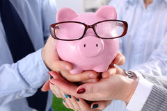 Businessman holding piggy box ,standing in office Stock Image