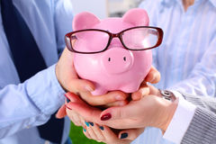 Businessman holding piggy box ,standing in office Royalty Free Stock Images