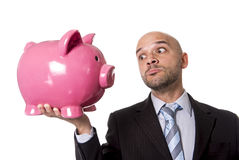 Businessman holding piggybank face to face looking the piggy bank in the eye Stock Image