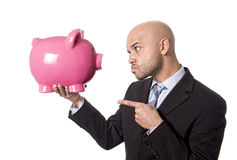 Businessman holding piggybank face to face pointing the piggy bank with his finger as a you better be full of money warning Royalty Free Stock Photography