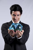 Businessman holding a piggybank full of coins Royalty Free Stock Photo