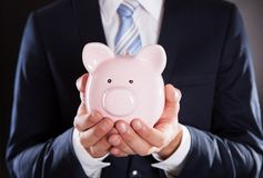 Businessman holding piggybank Royalty Free Stock Photos