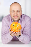Businessman Holding Piggybank In Office Stock Images