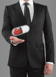 Businessman holding pills. With dollar symbol Royalty Free Stock Photography