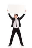 Businessman holding placard over his head. Stock Images
