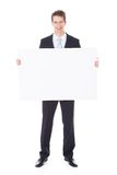 Businessman Holding Placard. Portrait Of Young Businessman Holding Blank Placard Over White Background Royalty Free Stock Image