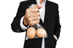 Businessman holding plastic bag with eggs, isolated on white background Stock Photo