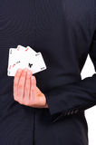 Businessman holding playing cards behind his back. Stock Photos