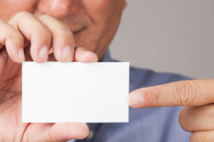 Businessman holding and pointing to a business card. A closed up shot of a businessman holding and pointing to a white blank business card Royalty Free Stock Photo