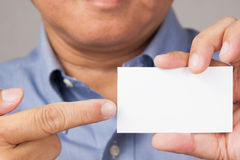 Businessman holding and pointing to a business card. A closed up shot of a businessman holding a white blank business card with thumbs up Royalty Free Stock Photography