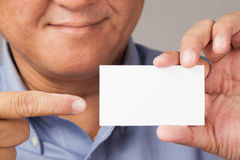 Businessman holding and pointing to a business card. A closed up shot of a businessman holding a white blank business card with thumbs up Royalty Free Stock Photos