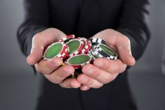 Businessman holding poker chips in cupped hands. Midsection of businessman holding poker chips in cupped hands against gray background stock photo