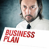 Businessman holding poster with business plan printed title Royalty Free Stock Photo