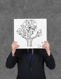 Businessman holding poster with money tree Stock Photo